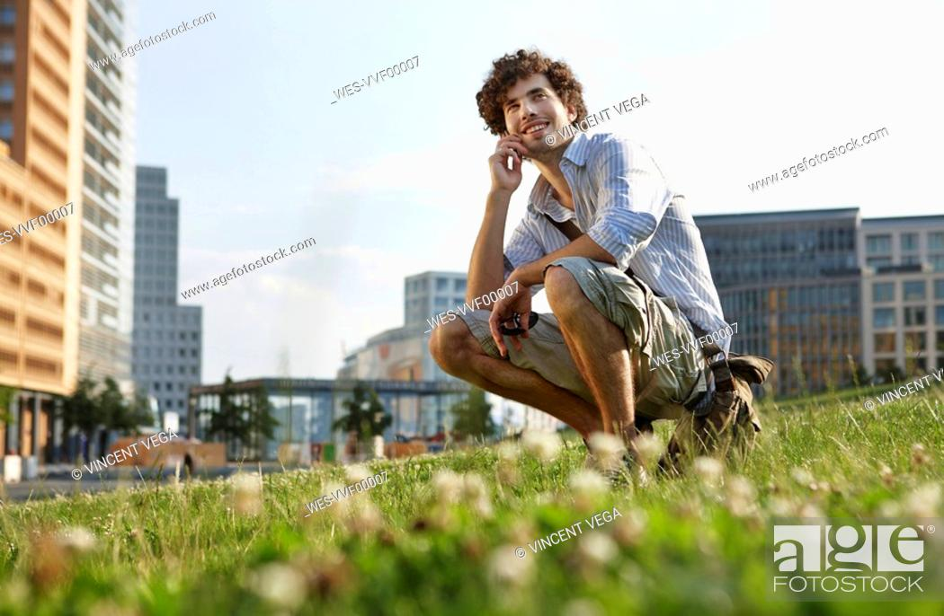 Stock Photo: Germany, Berlin, Young man using mobile phone, smiling, portrait.