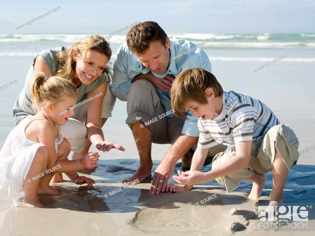 Stock Photo: Family looking in sand.