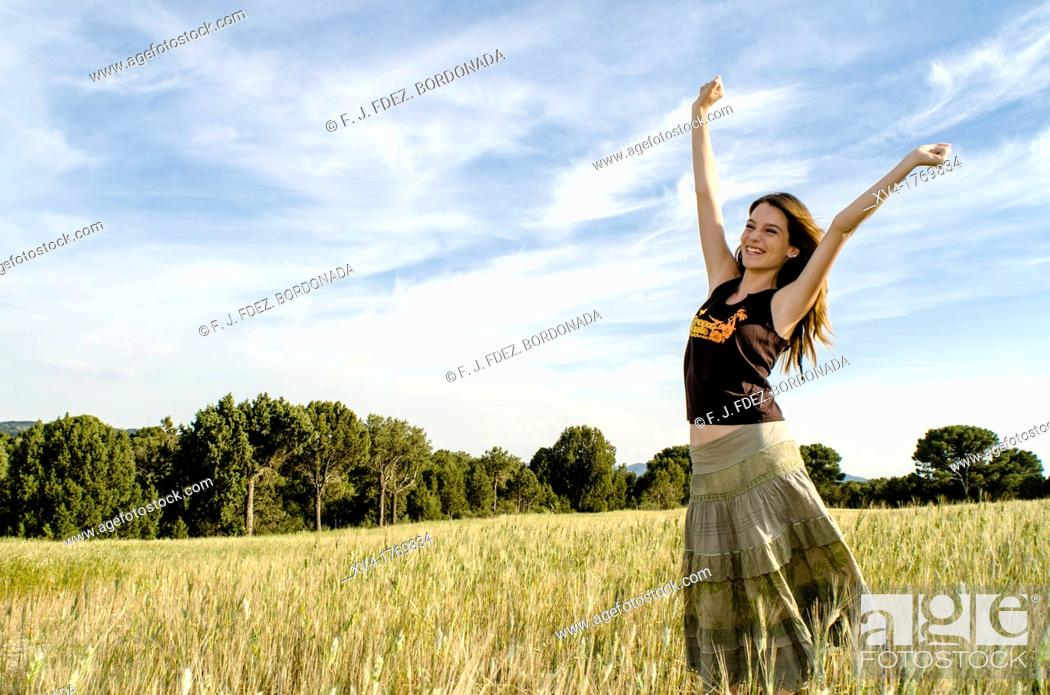 Stock Photo: Pretty girl relaxing and enjoy in the wheat field.