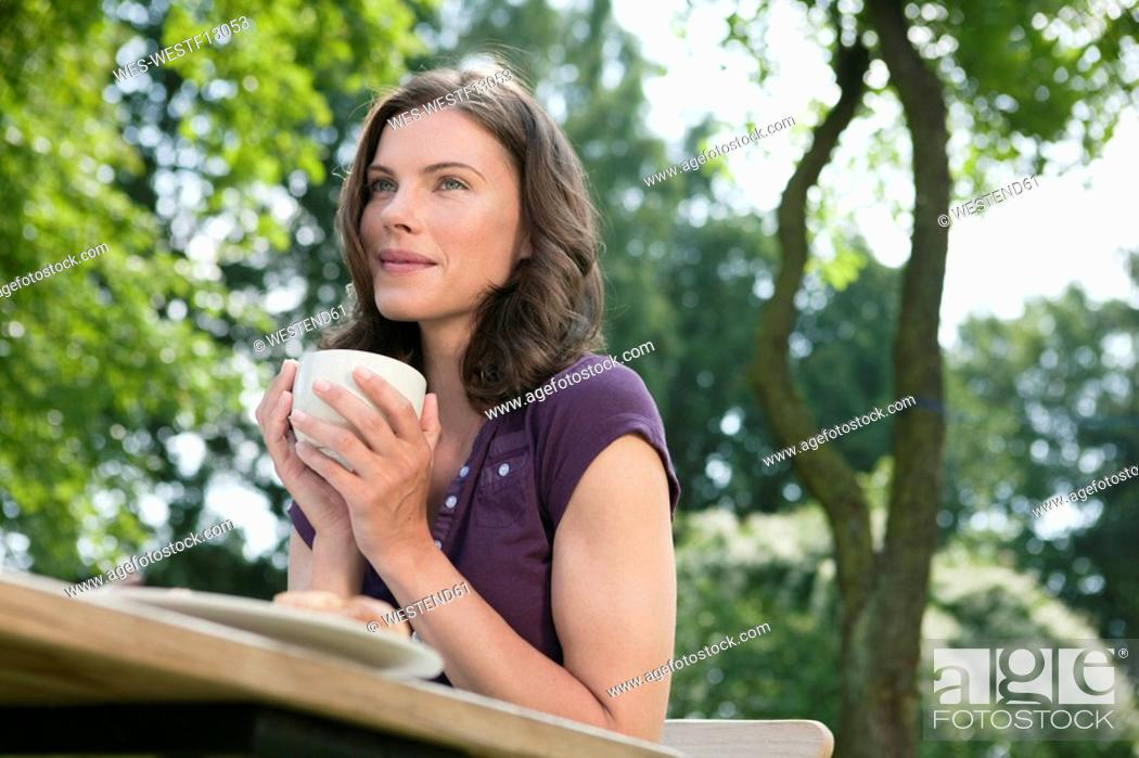 Stock Photo: Germany, Hamburg, Woman in garden holding cup of coffee, low angle view.