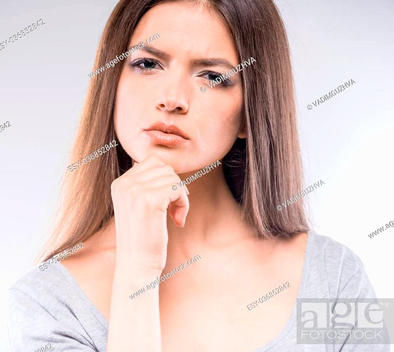 Stock Photo: Lost in thoughts. Thoughtful young woman holding hand on chin while standing against grey background.