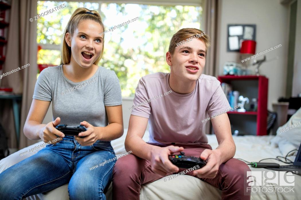 Stock Photo: Happy teenage girl and boy sitting on bed playing video game.