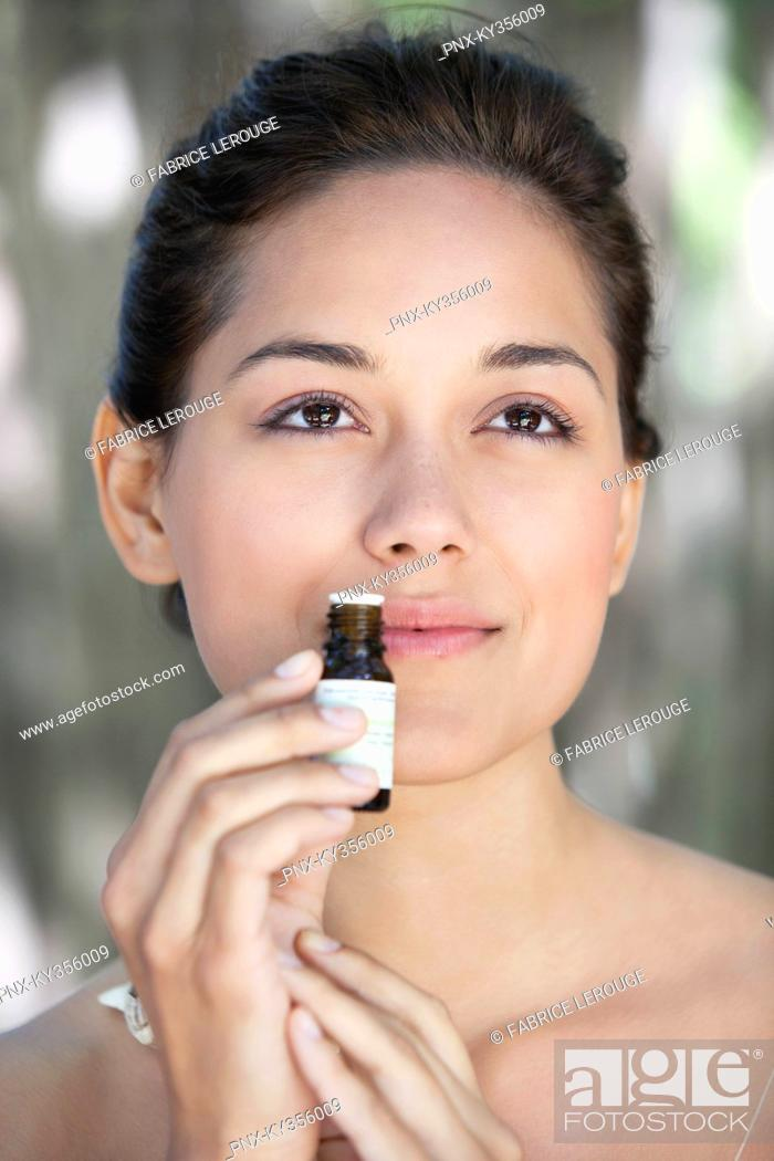 Stock Photo: Young woman smelling aromatherapy oil.