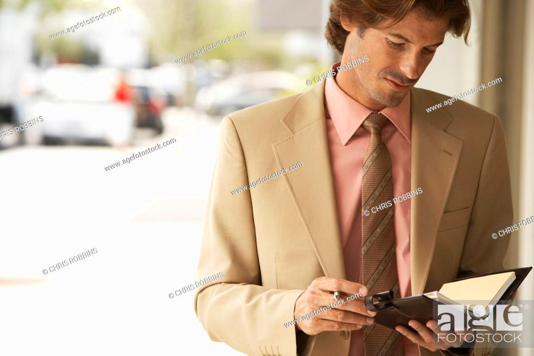 Stock Photo: Businessman reading diary in street close-up.