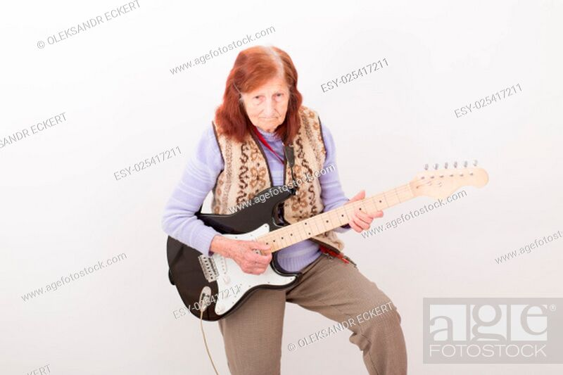 Stock Photo: Funny elderly lady plays passionate electric guitar.