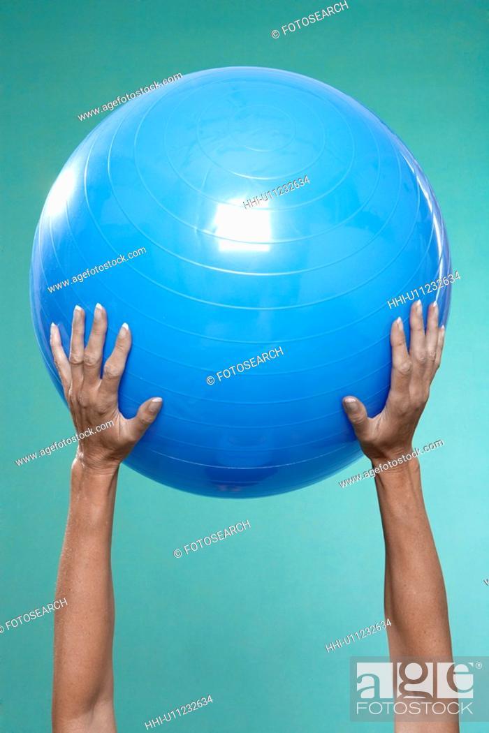 Stock Photo: Mature woman holding Swiss ball (close-up).