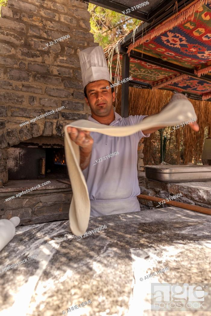 Stock Photo: Turkish pide baker baking pide for tourists at an outdoor kitchen at the beach. Near Bodrum, Turkish Riviera, Turkey, Eurasia, .