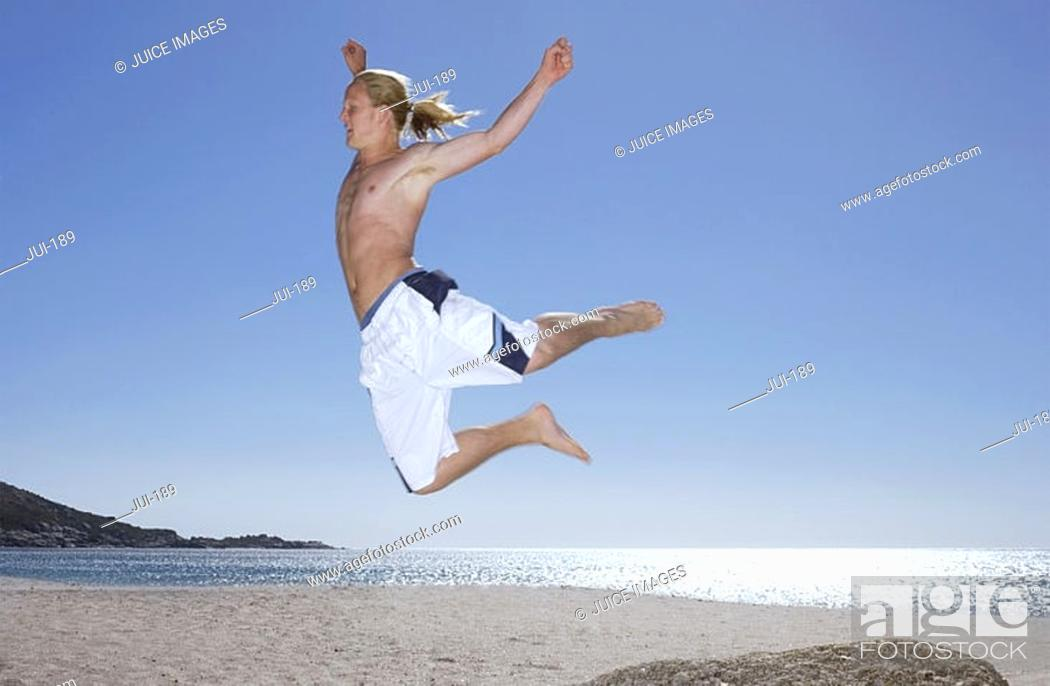 Stock Photo: Teenage boy 17-19 in white swimming shorts leaping from rock on beach, side view.