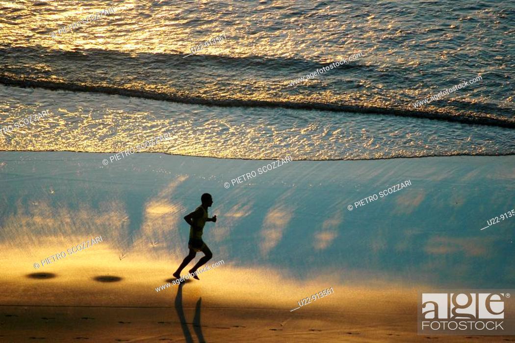 Stock Photo: Jericoacoara (Ceara, Brazil): a man jogging at sunset along the beach.
