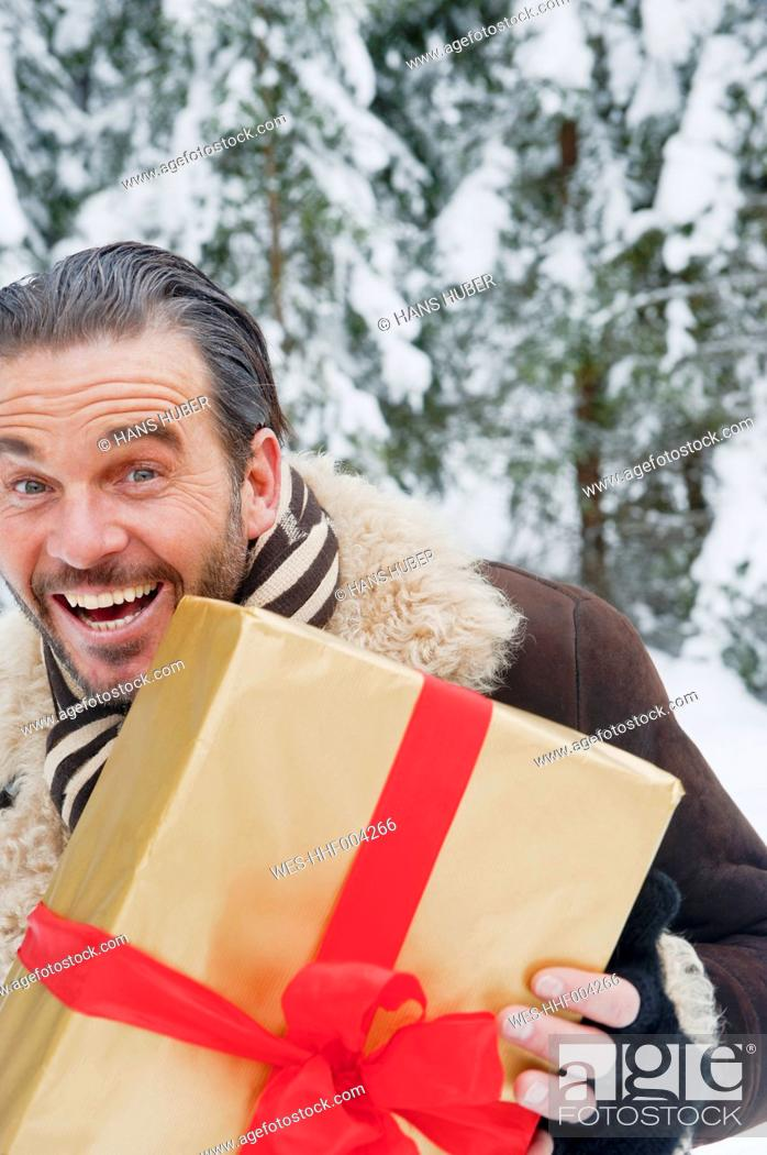 Stock Photo: Austria, Salzburg County, Mature man standing with christmas parcel, smiling, portrait.