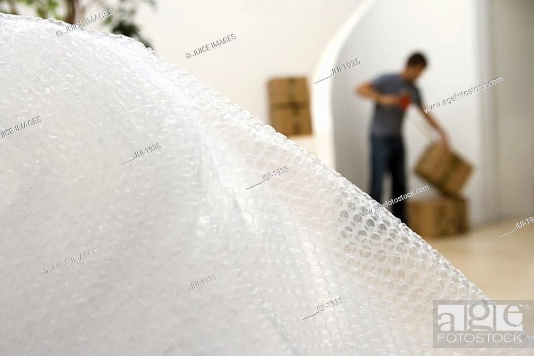 Stock Photo: Man sealing box with tape at home, focus on bubble wrap in foreground.