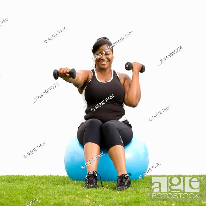Stock Photo: Plus size model working out with weights on cardio ball.