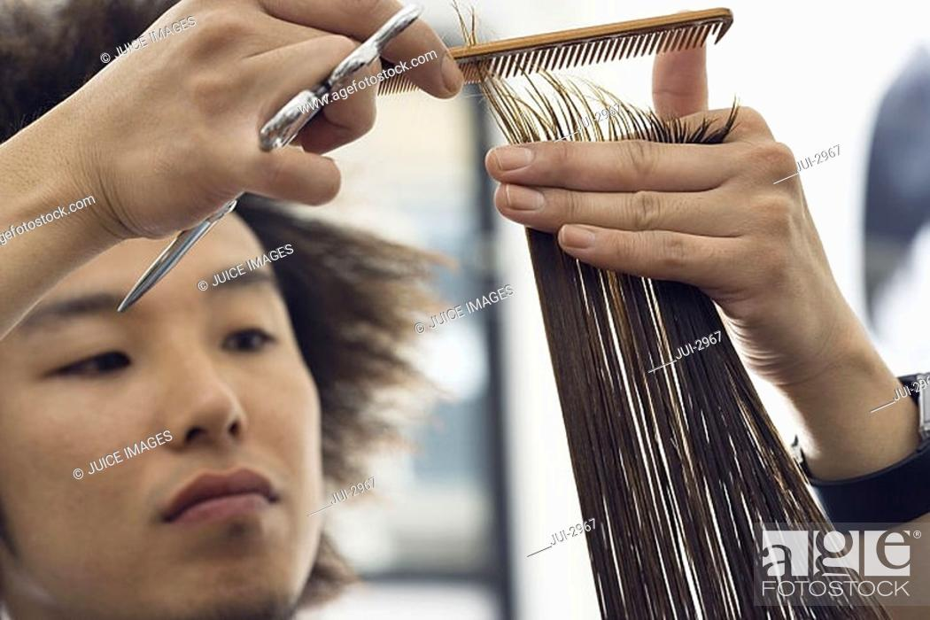 Stock Photo: Young male hairdresser cutting woman's hair in salon, close-up, focus on foreground.