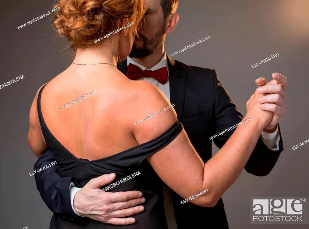 Imagen: Passionate middle-aged man and woman dancing. Focus on woman back wearing black dress. Isolated.