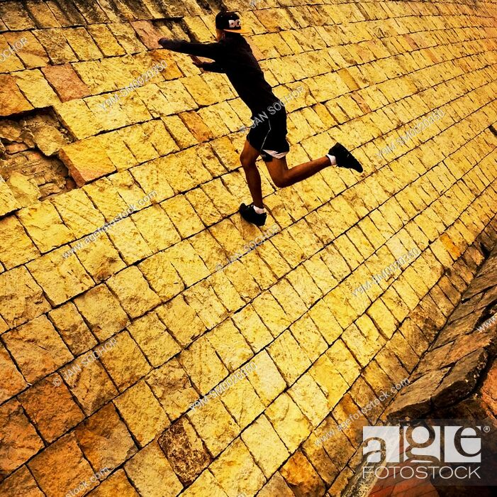 Stock Photo: A Colombian parkour runner jumps on the wall during a free running training session held in a park in Kennedy, Bogotá, Colombia, 20 February 2016.