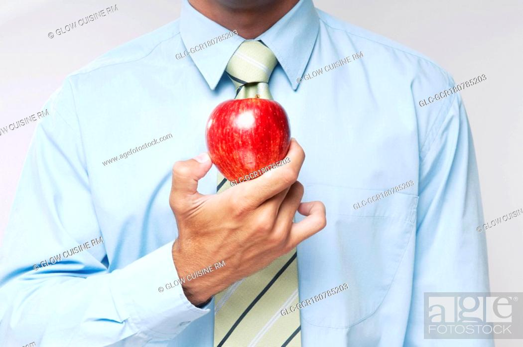 Stock Photo: Mid section view of a businessman holding a red apple.
