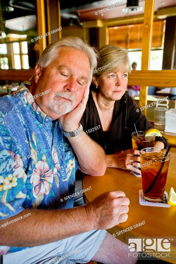 Stock Photo: A middle aged couple appeared indifferent to each others' company over iced tea together in a Long Beach, CA, restaurant.