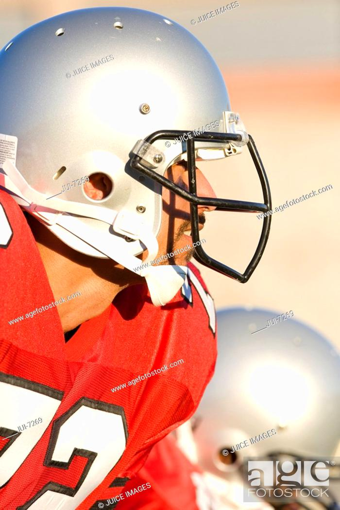 Stock Photo: American football player wearing red football strip and protective helmet, close-up, profile, focus on foreground.