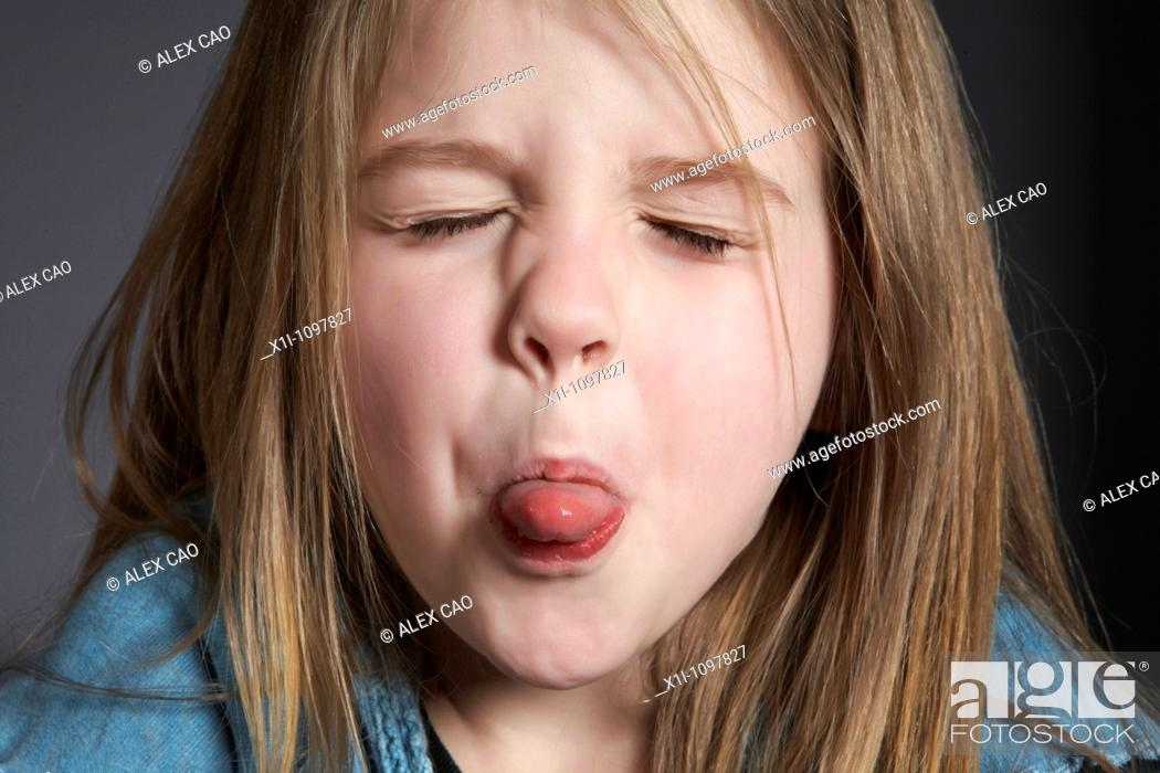 Stock Photo: Girl sticking out tongue.