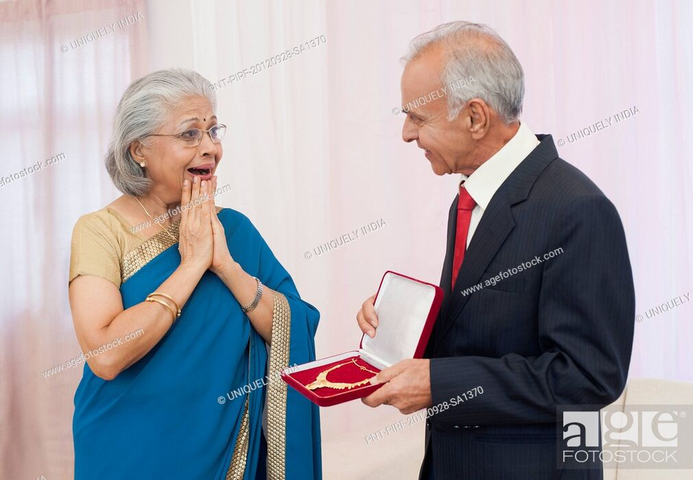 Stock Photo: Man giving jewelry to his wife on their anniversary.