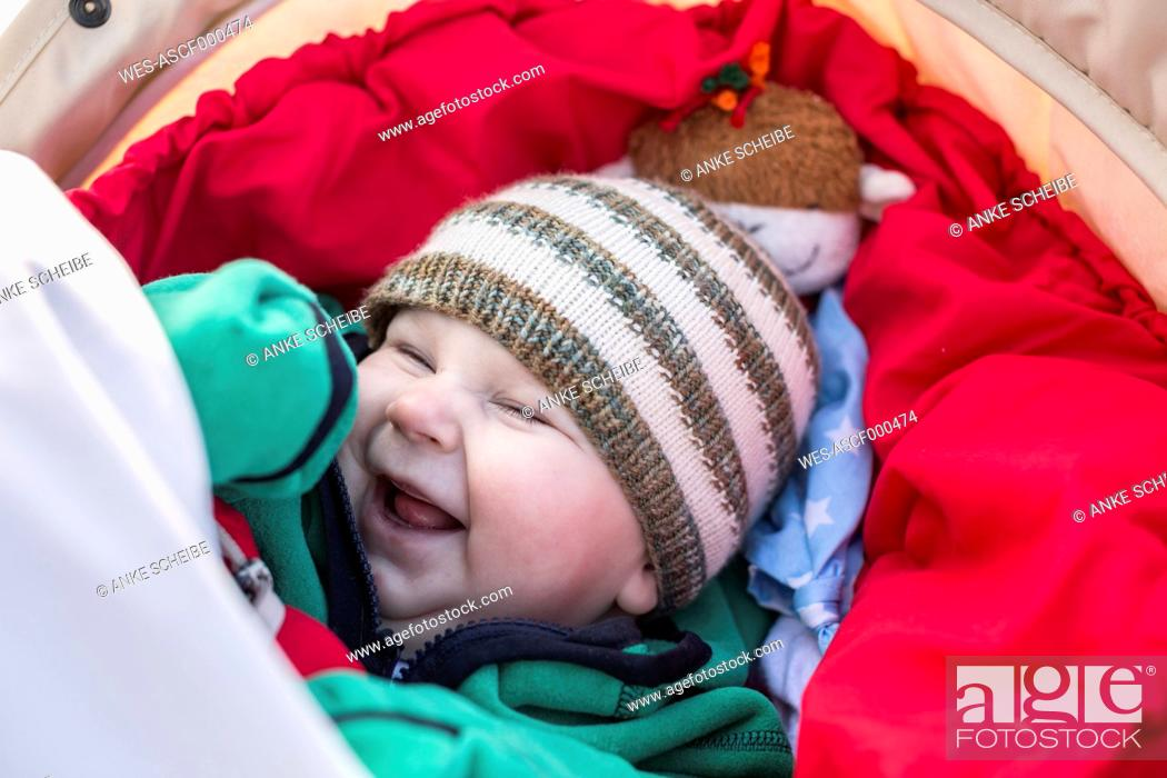 Stock Photo: Portrait of laughing baby boy wearing woolly hat.