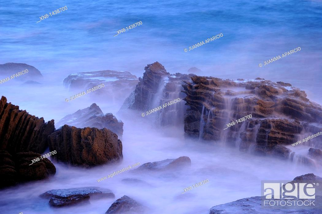 Stock Photo: Night photography with long exposure time of sea water breaking on rocks in the Bahia de la Concha in San Sebastian, Spain.