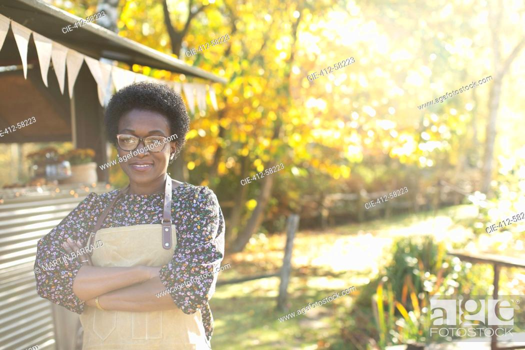 Photo de stock: Portrait confident female food cart owner in sunny autumn park.