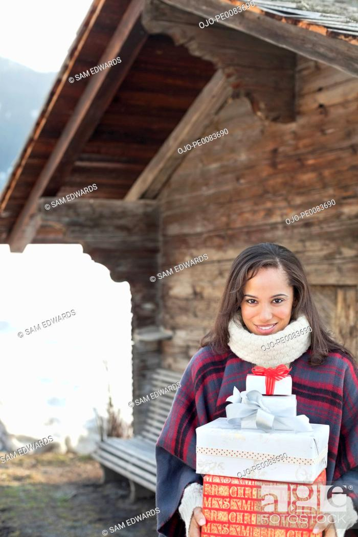 Stock Photo: Portrait of smiling woman holding Christmas gifts in front of cabin.