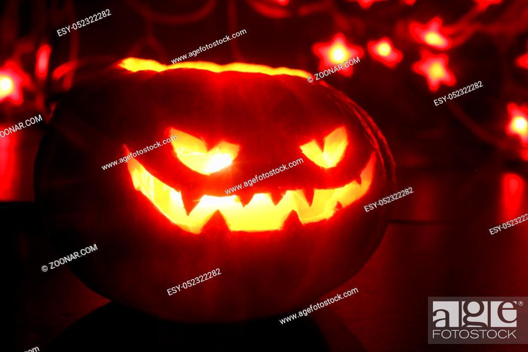 Stock Photo: Illuminated cute halloween pumpkin and red bokeh lights on black background.