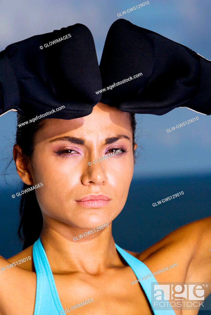 Stock Photo: Portrait of a young woman wearing boxing gloves.