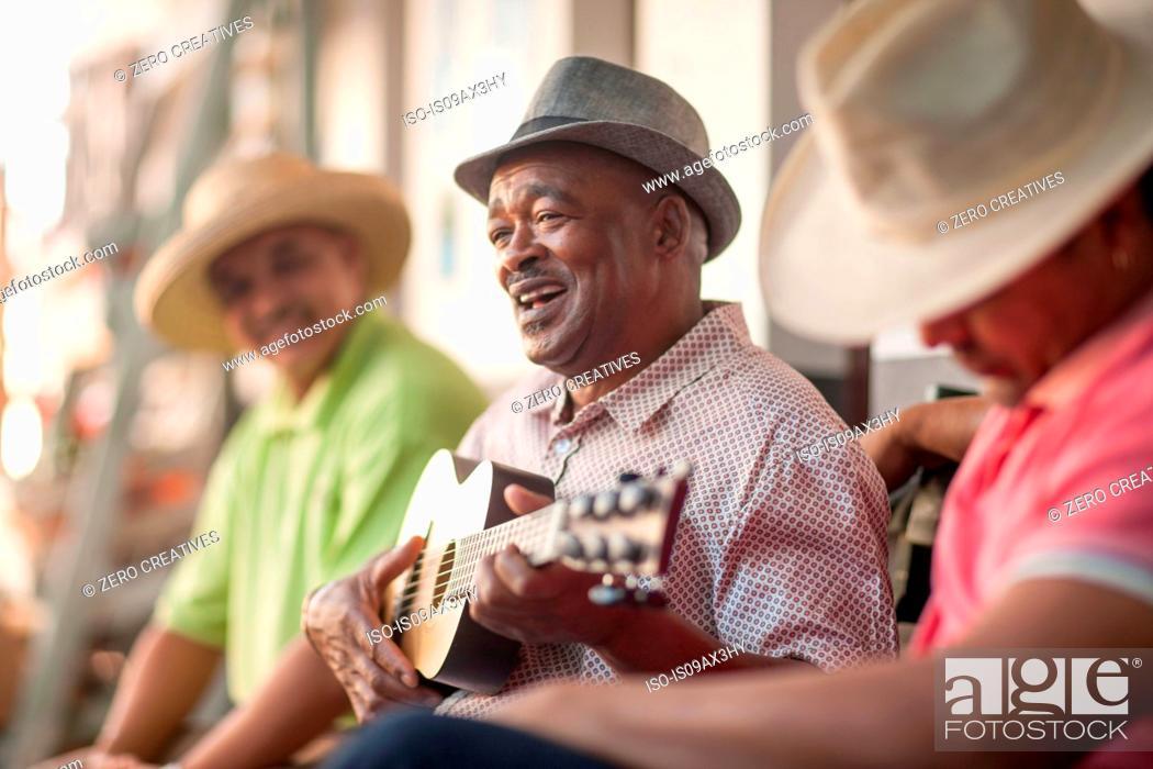 Imagen: Man playing ukulele, entertaining friends.