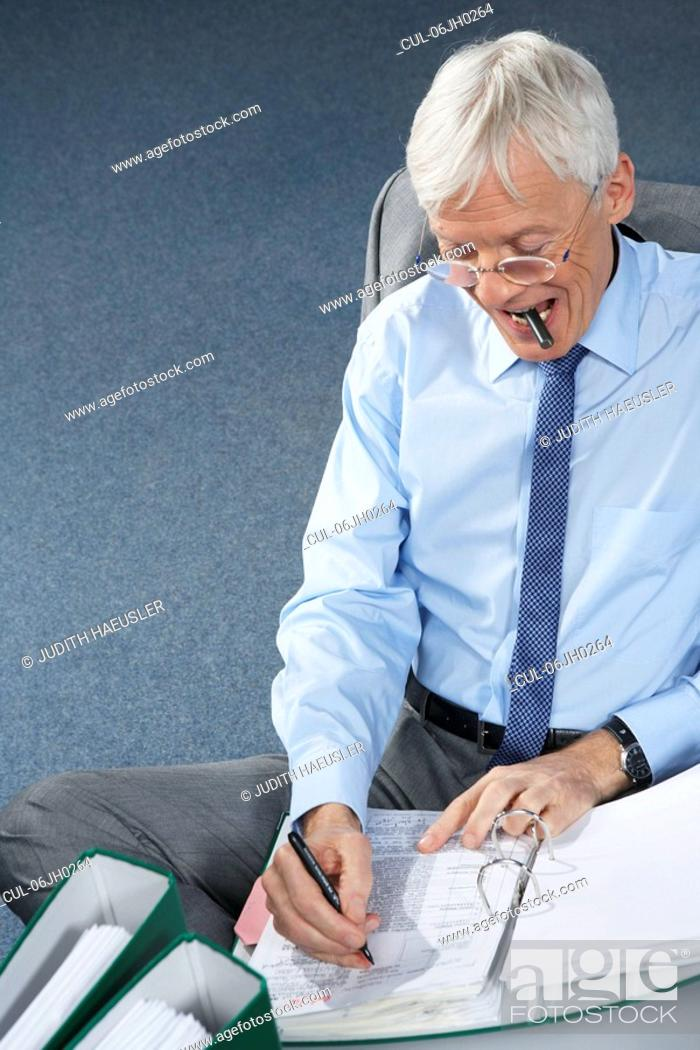 Stock Photo: Mature businessman writing.