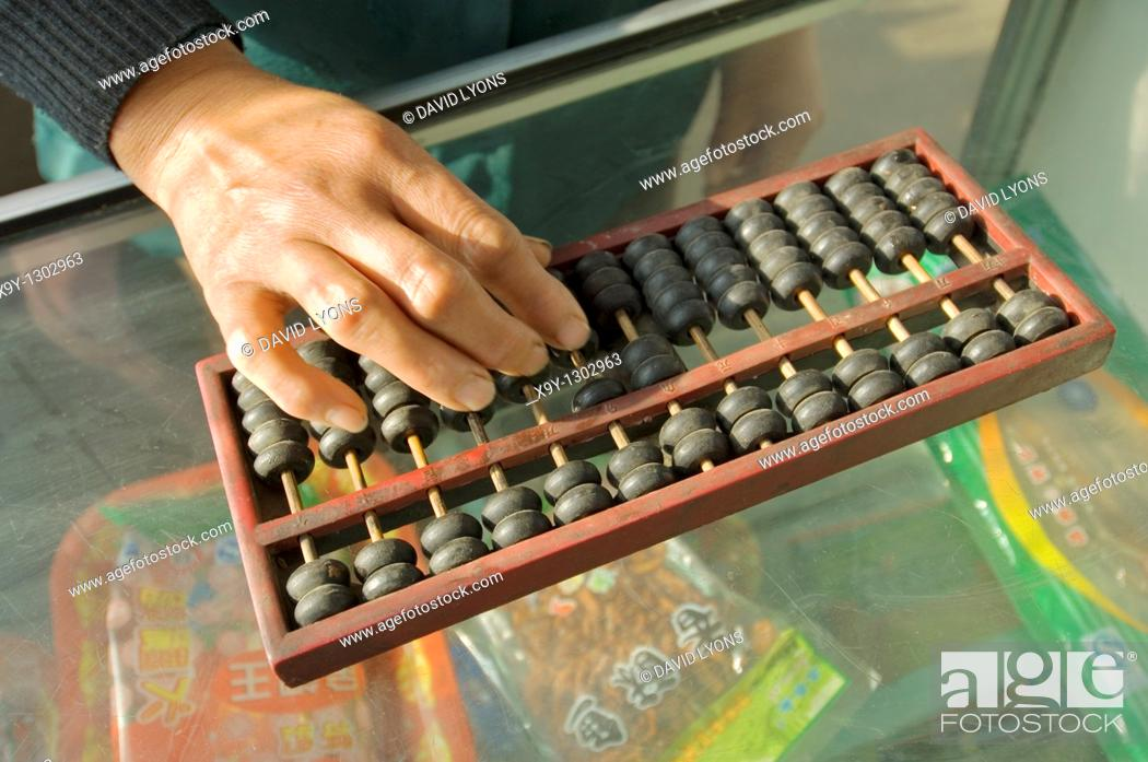 Stock Photo: Abacus counting machine calculator  Woman hand using abacus adding subtracting sum on shop counter in Chinese shop, China.