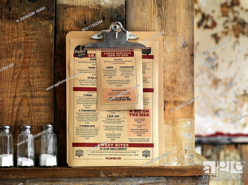 Stock Photo: A menu consisting of pulled pork dishes leaning against a rustic wooden wall (USA).