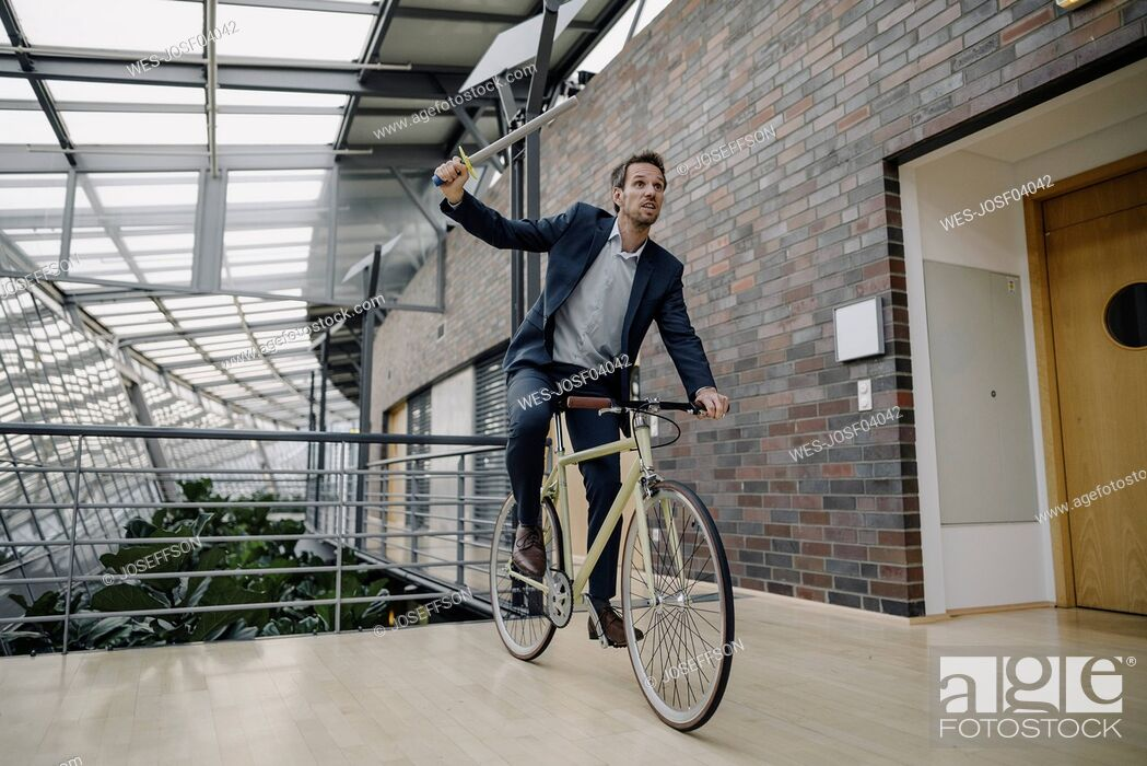 Stock Photo: Businessman holding a toy sword and riding bicycle in modern office building.