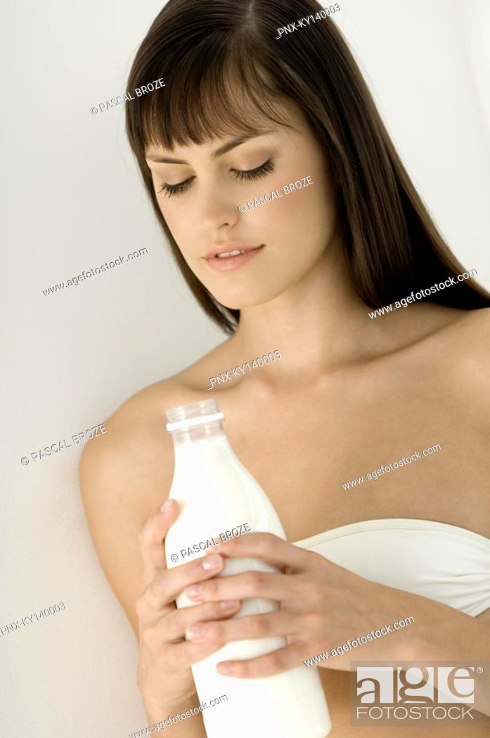 Stock Photo: Portrait of a young woman holding bottle of milk.