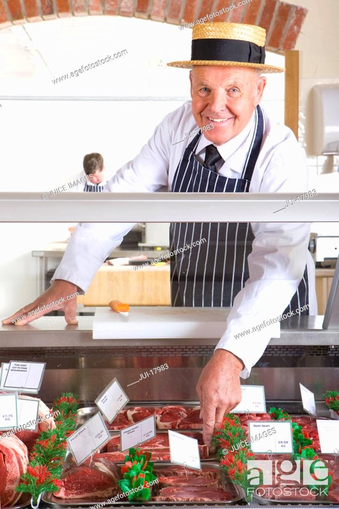 Stock Photo: Butcher in uniform behind meat counter.