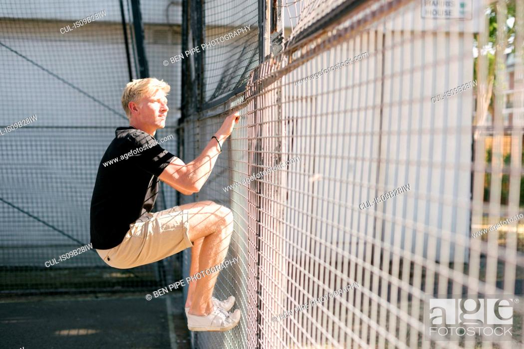 Stock Photo: Young man climbing wire fence.