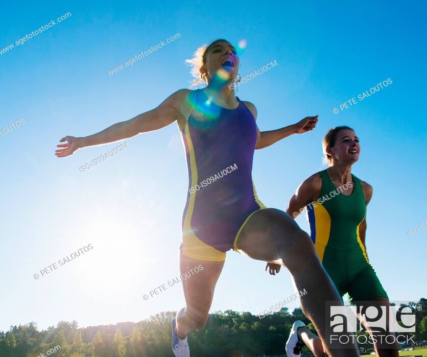 Photo de stock: Two female athletes on athletics track, at end of race.