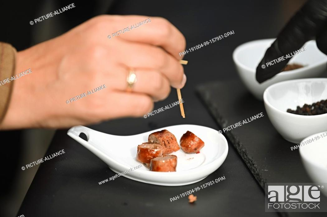 Stock Photo: 04 October 2019, Bavaria, Kulmbach: Bavarian Agriculture Minister Michaela Kaniber (CSU) is trying a refined pork sausage.