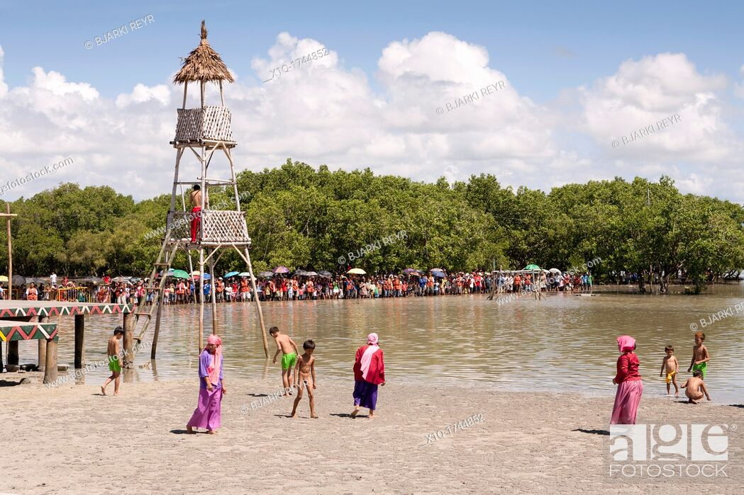 Stock Photo: Women and children on the beach before the battle begins at the Battle of Mactan reenactment or Kadaugan Festival  The Battle of Mactan was fought in the.