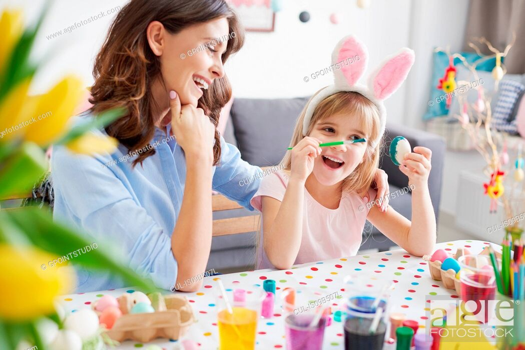 Stock Photo: Woman and daughter painting easter eggs at table.