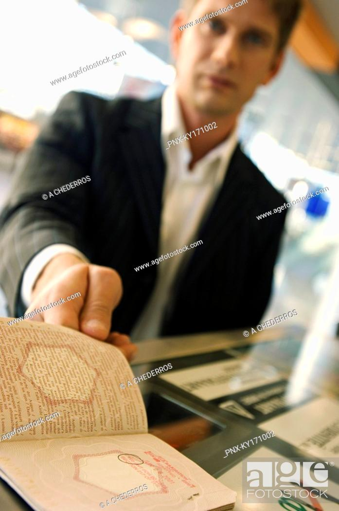 Stock Photo: Businessman showing his passport at the airport check-in counter.
