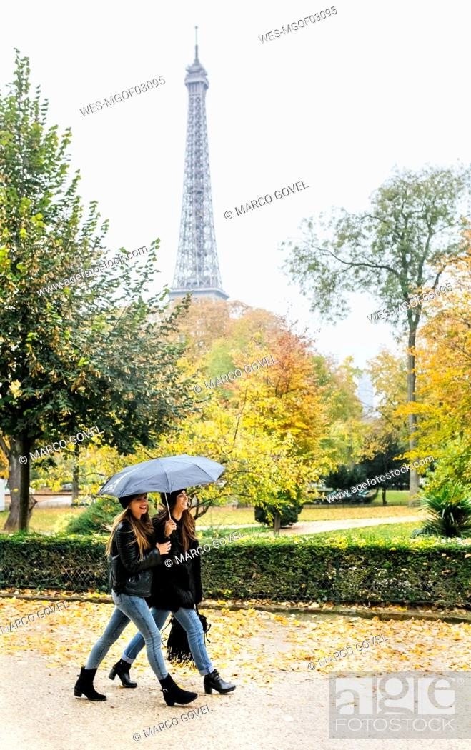 Stock Photo: France, Paris, two young women walking in park with the Eiffel Tower in the background.
