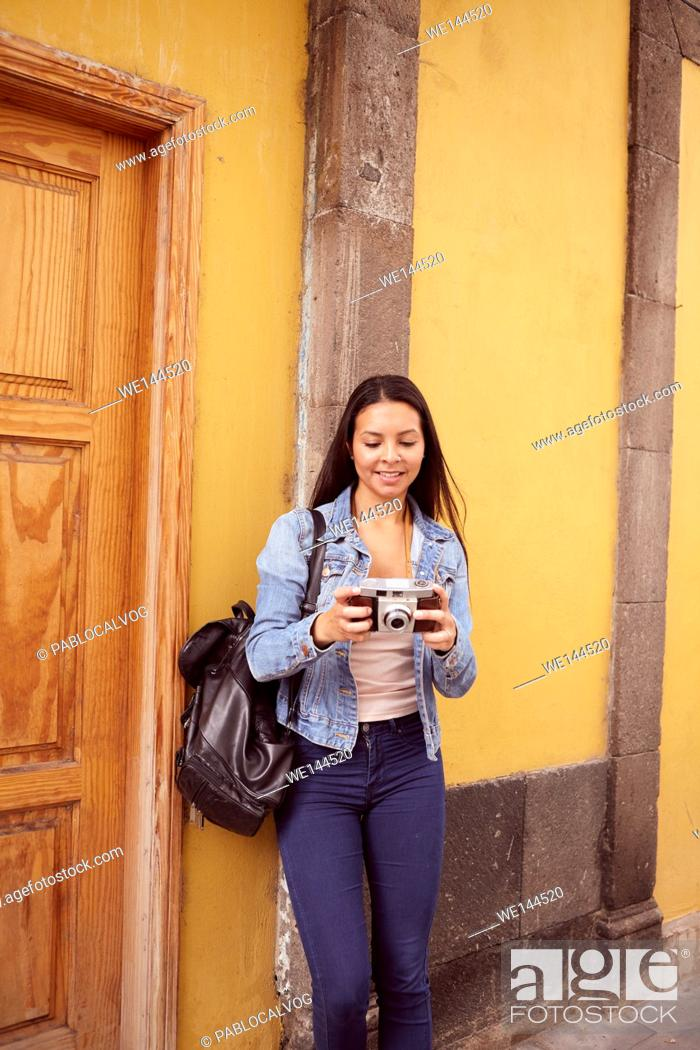 Stock Photo: Pretty young girl leaning against a gray pillar smiling at her camera with old yellow buildings behind her in casual jeans and denim jacket.