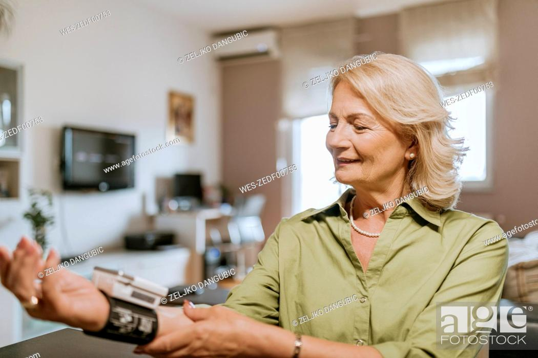Stock Photo: Smiling senior woman taking her blood pressure.