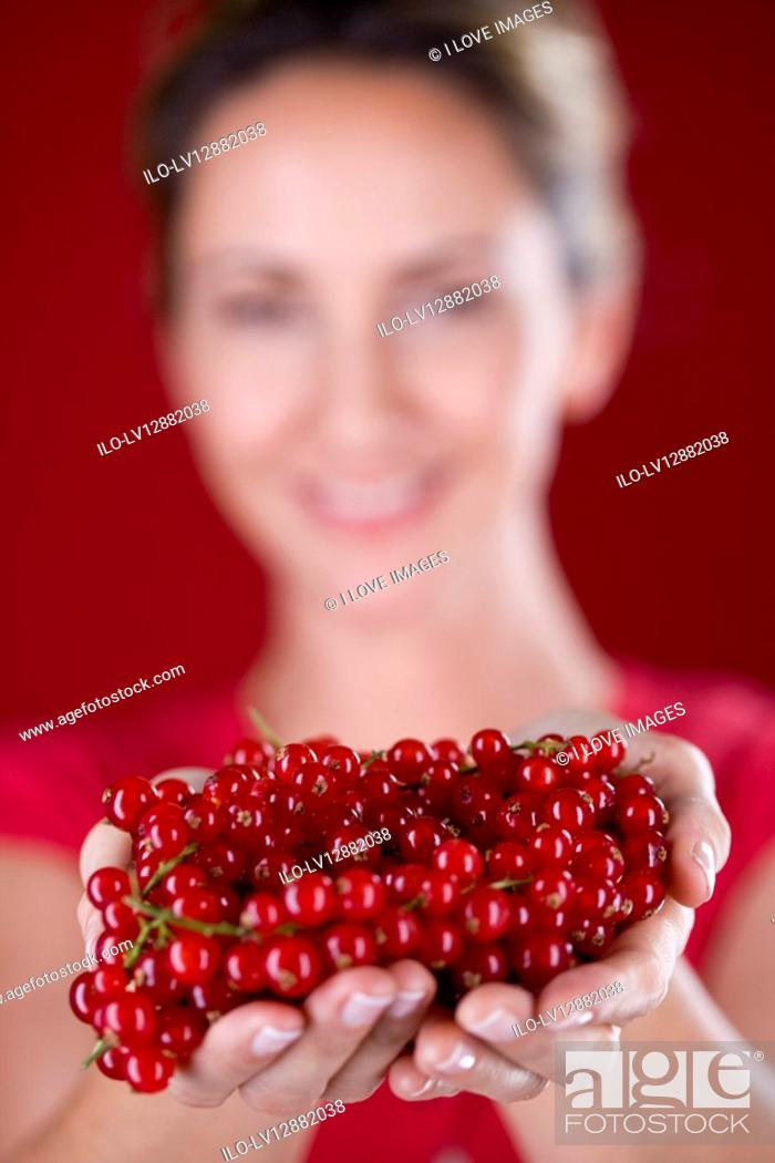Stock Photo: A mid adult woman holding a handful of redcurrants.