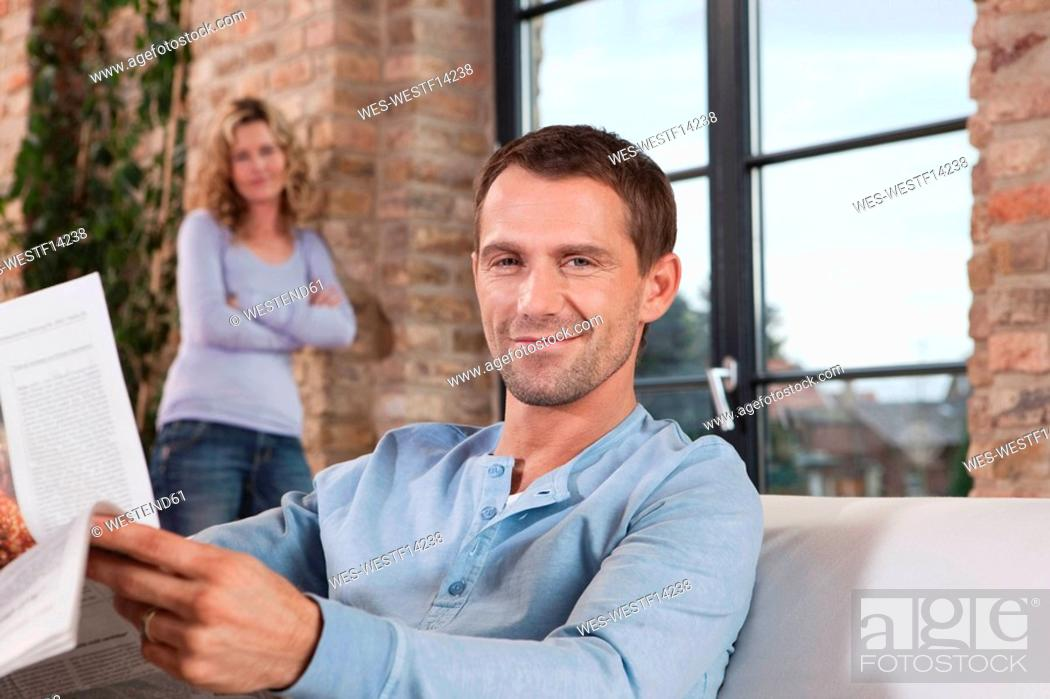 Stock Photo: Germany, Cologne, Couple, man on sofa holding newspaper, woman standing in background, portrait, close-up.