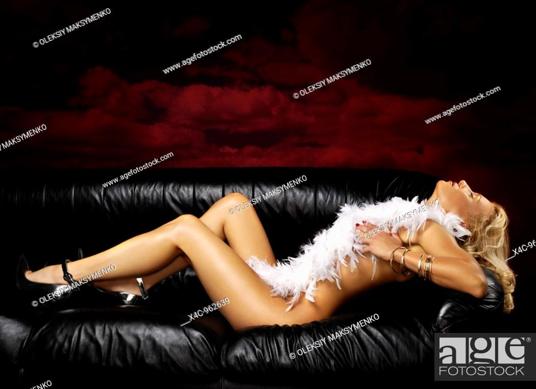Stock Photo: Beautiful naked woman with white feathers lying on black leather couch.