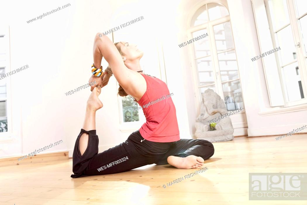 Stock Photo: Woman in yoga pose stretching herself.